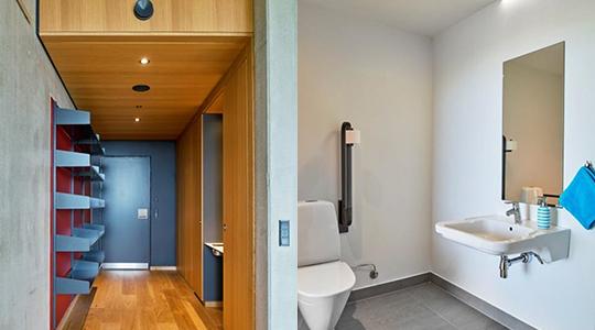 Venstre side af billedet viser lejlighedens entré med opbevaring, køleskab og vask. Højre side viser lejlighedens badeværelse med tilgængeligt toilet, håndvask og spejl.