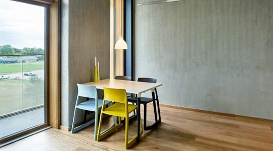 På billedet ses lejlighedens spiseplads med bord, stole og panoramavindue ud til altanen.