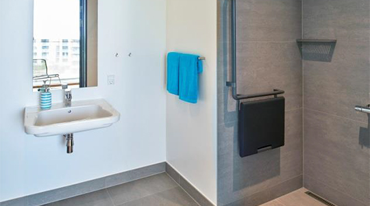 The image shows the bathroom with a sink and mirror to the left and shower stall to the right.